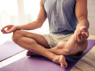 Man sitting and meditating on yoga mat.
