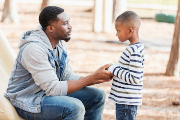 Father talks with son on playground.