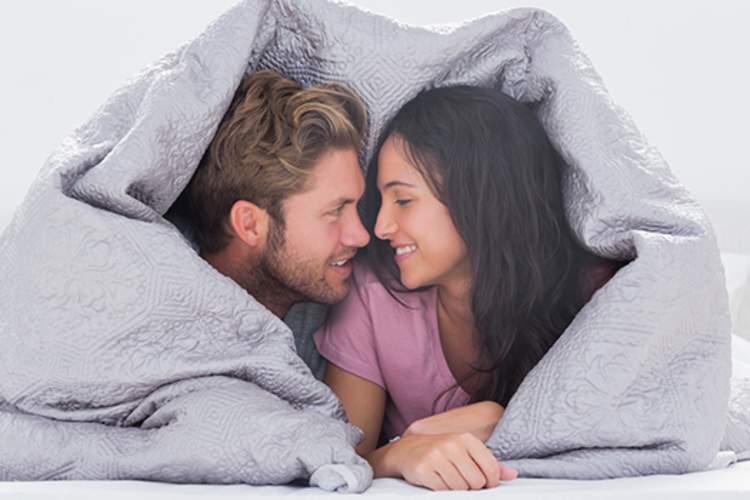 Young couple in bed under covers.