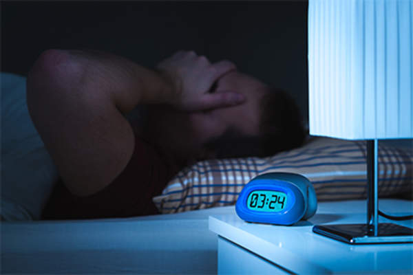 Man having trouble sleeping in bed.