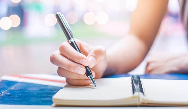 Woman writing with pen in notebook.