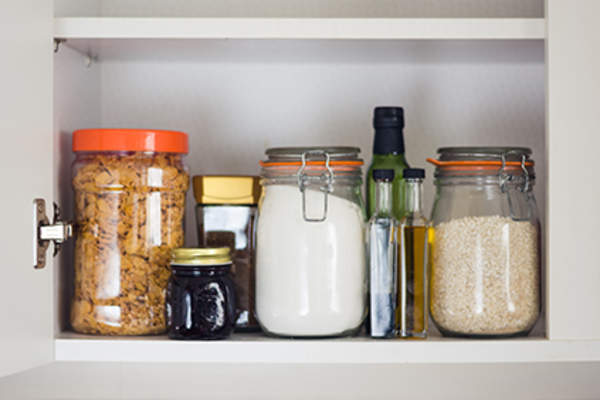 Food stored in containers in a pantry.