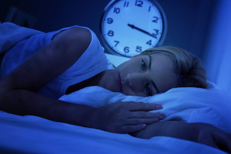 Woman laying in bed in the dark suffering from insomnia.