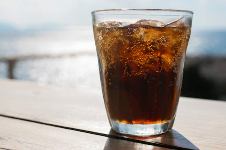 A glass of diet soda on a table.