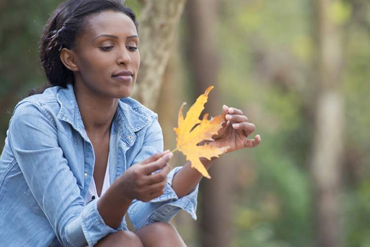 Woman sitting, thinking, and holding a fallen leaf.