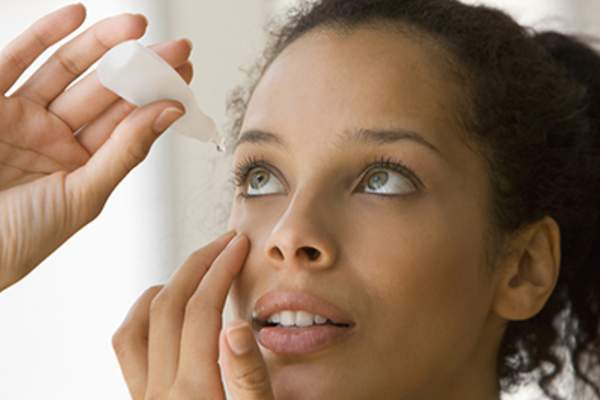 Young woman putting drops in dry eyes.