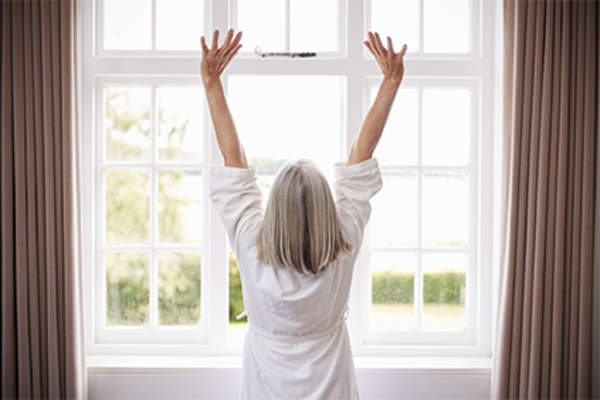 Healthy senior woman stretching with arms up.