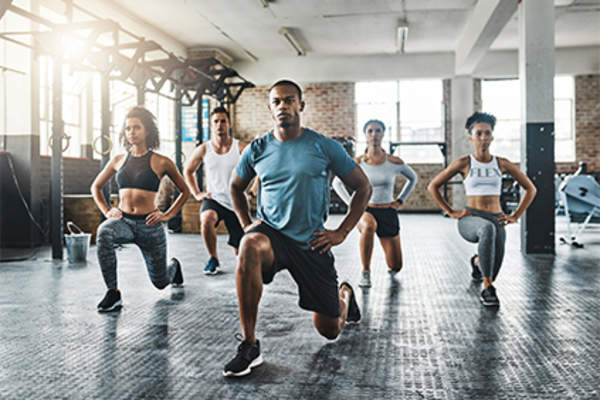 Group of people doing isometric lunges in exercise class.