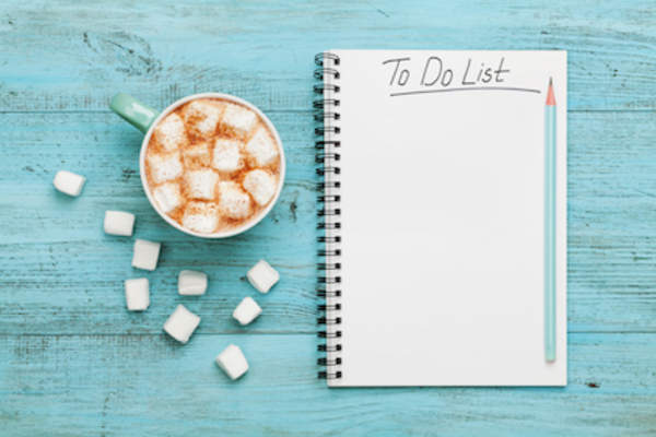 To do list notebook next to a cup of hot cocoa.