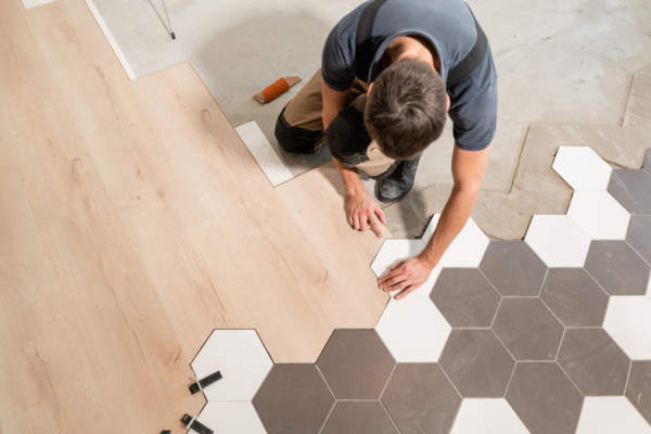 man installing tile flooring next to wood flooring