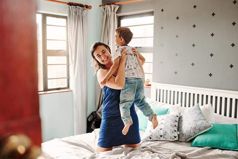 Mother and son jumping on the bed
