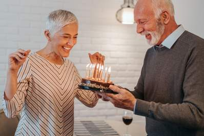 Senior couple celebrating special occasion with cake and candles.