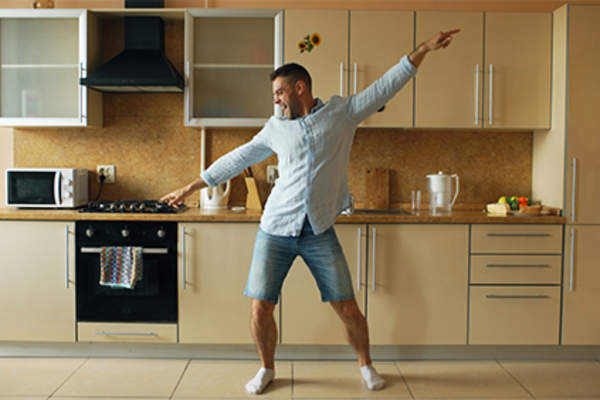 Man dancing in his kitchen at home.