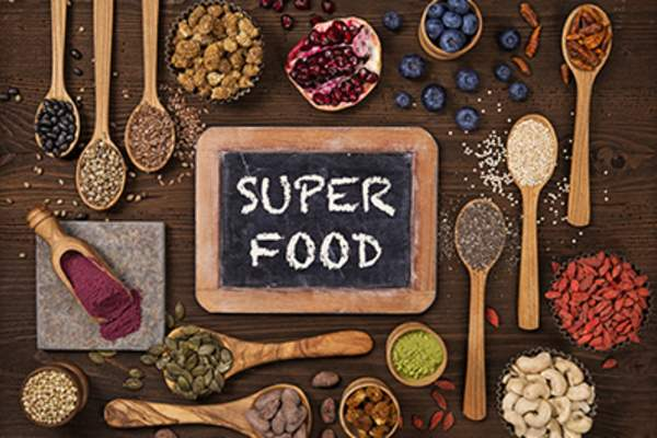 Various superfoods surrounding a chalkboard.