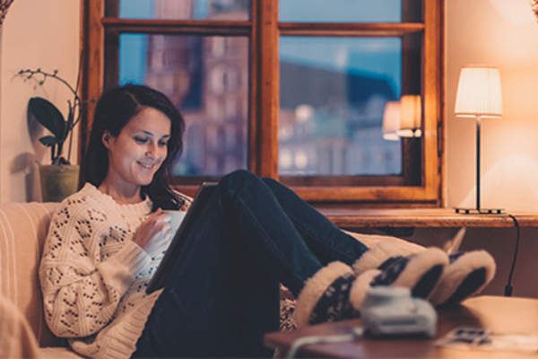 Young woman on electronic device sitting on the couch at home in the evening.