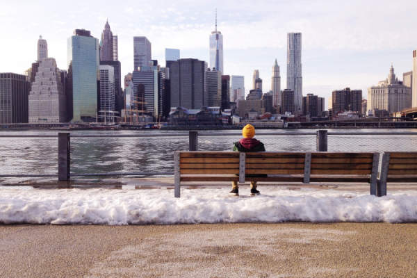 person sitting on bench surrounded by melting snow