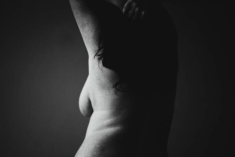 black and white image of topless woman from behind