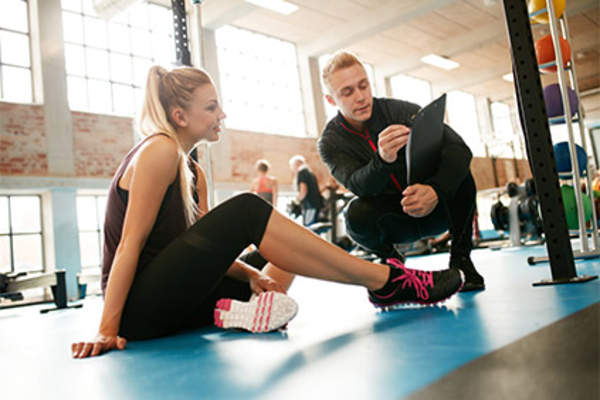 Fitness trainer working with young woman in gym on mat.