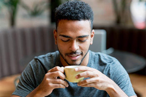 Young man drinking coffee in cafe.