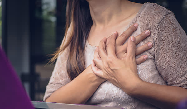 Woman holding her chest while experiencing chest pain.