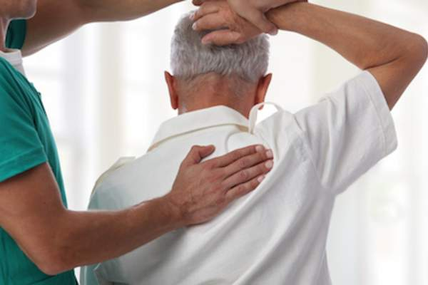 Physical therapist helping patient with shoulder range of motion.