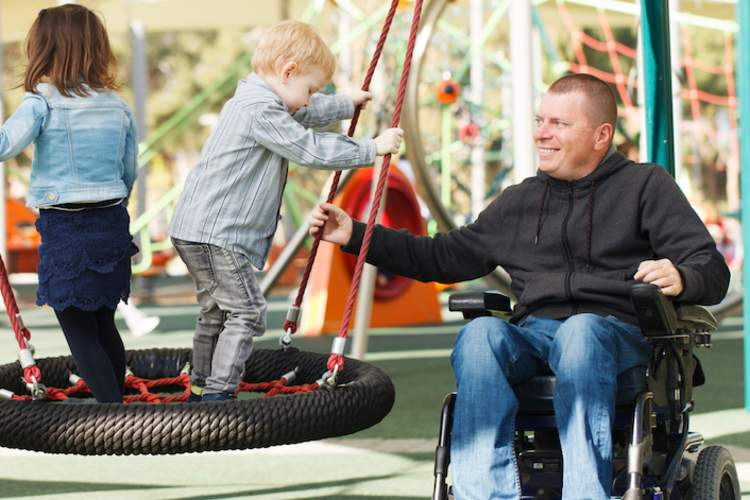 Man in wheelchair at playground with children.