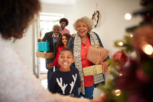 Grandparents Being Greeted By Family As They Arrive For Visit On Christmas Day With Gifts