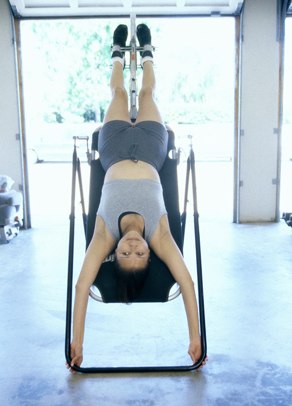 Woman using an inversion chair.