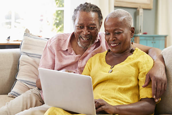 Senior couple researching medicare on a laptop.