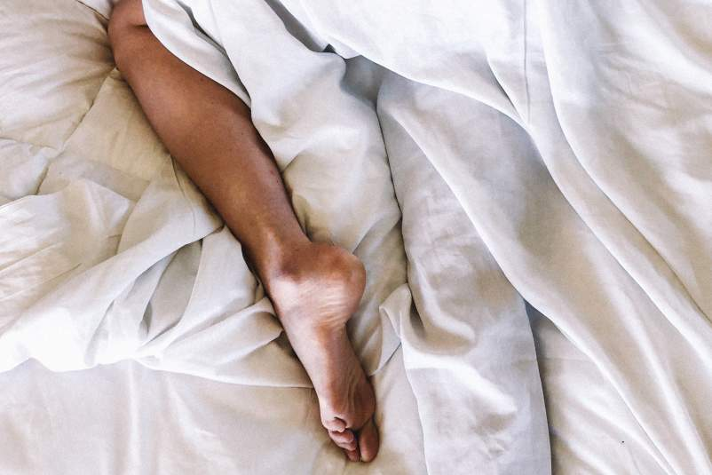 Leg of woman asleep in bed under covers.