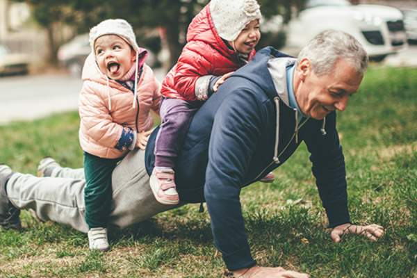 Older man doing pushups with grandchildren on his back image.