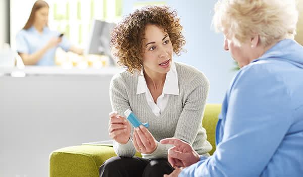 Woman explaining how to use inhaler to senior.