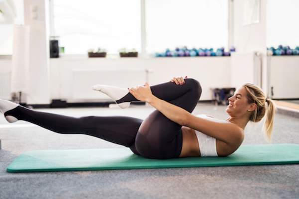 Woman working hard in pilates class.
