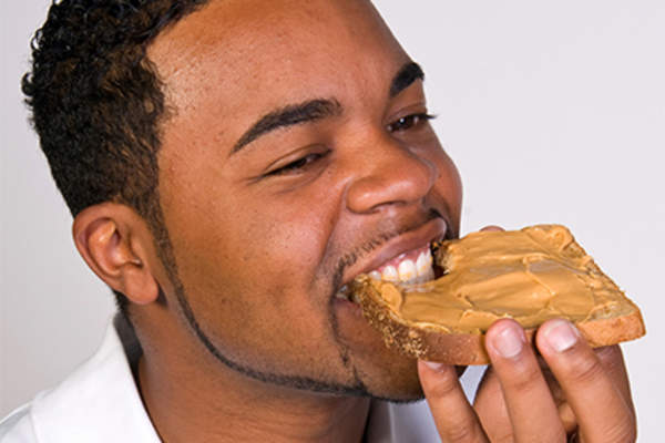Young man eating whole-grain peanut butter toast.
