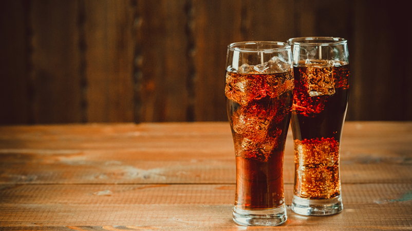 Two ice cold glasses of soda on wood table.