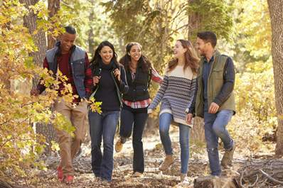 Group of young adult friends hiking in the woods and laughing and talking