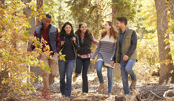 Young group of friends hiking in the woods and talking and laughing