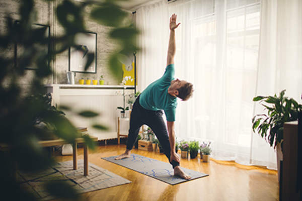 Man doing yoga in his living room.