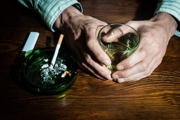 Cigarette in ashtray hands holding a whiskey.