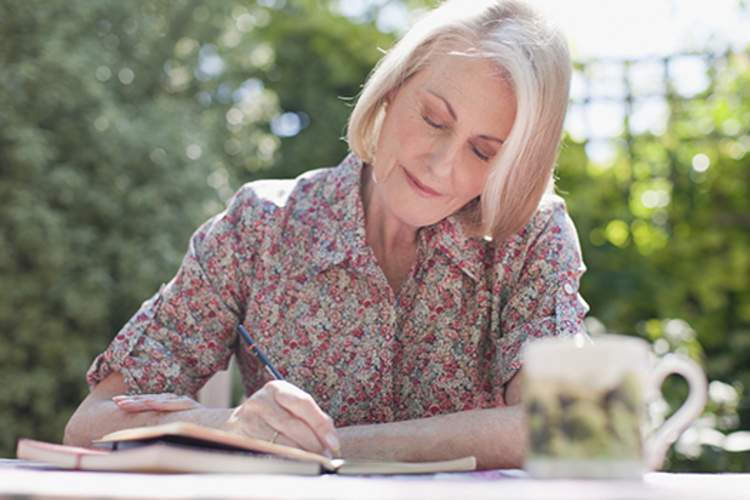 Mature woman writing in a journal.