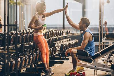 Man and woman high five at gym after workout.