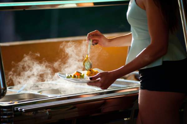 woman getting healthy foods from buffet