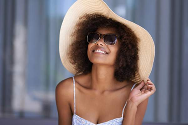 Smiling woman wearing sunglasses and a sun hat.