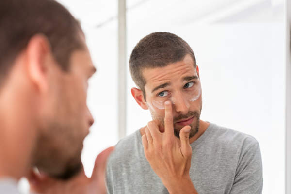 man putting on face cream in mirror