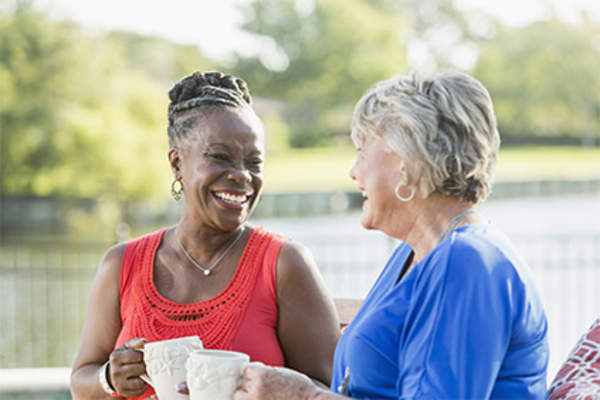 Two senior women enjoying a cup of coffee outside.