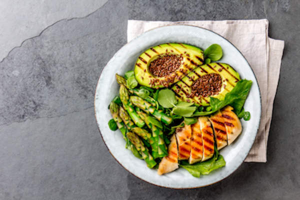 Healthy grilled chicken, grilled avocado and asparagus salad with linen seeds.