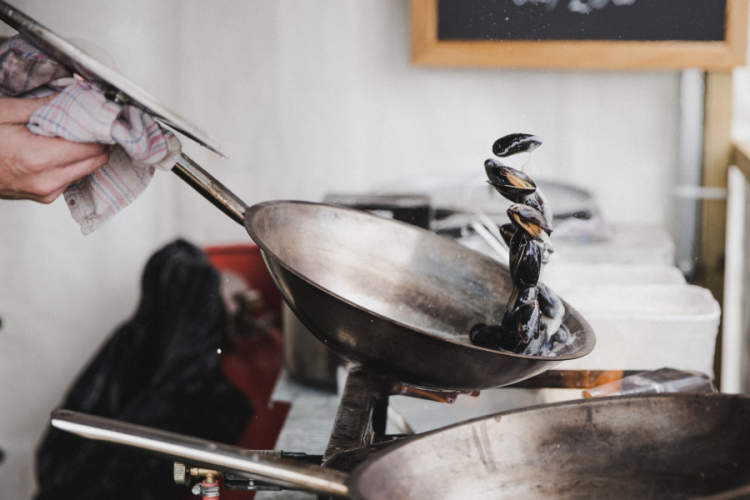 person cooking mussels in a pan