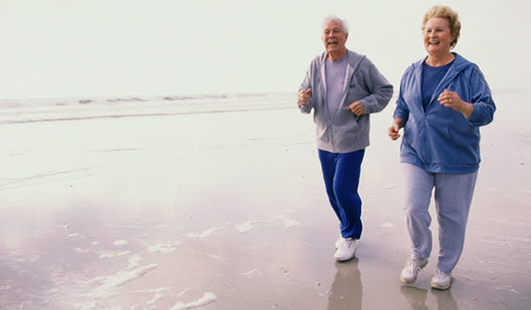 Senior couple jogging on the beach