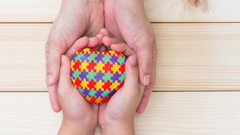 Adult and child holding autism awareness colored heart puzzle.