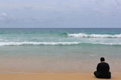Lonely woman sitting on empty beach.